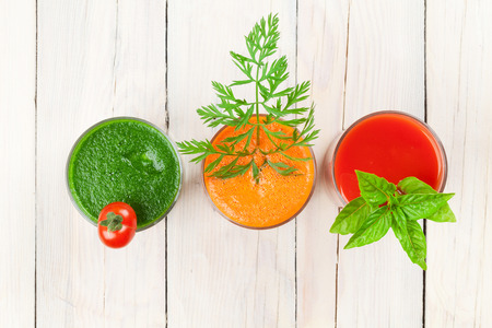 tomato: Fresh vegetable smoothie on wooden table. Tomato, cucumber, carrot. Top view
