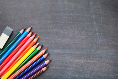 teaching crayons: School supplies on blackboard background. Top view with copy space