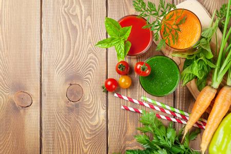 verduras verdes: Batido de verduras frescas en la mesa de madera. Tomate, pepino, zanahoria. Vista superior con espacio de copia