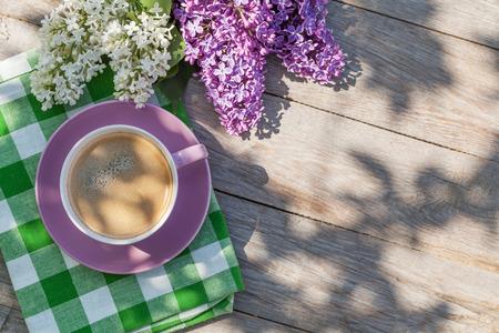 planta de cafe: Taza de café y coloridas flores de color lila en la mesa de jardín. Vista superior con espacio de copia