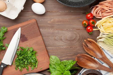 wooden table top view: Pasta cooking ingredients and utensils on wooden table. Top view with copy space Stock Photo