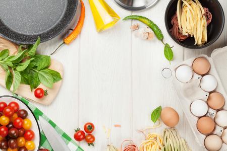 Ingredientes para cocinar Pasta y utensilios de mesa de madera. Vista superior con espacio de copia