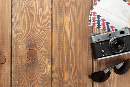office space: Camera, letters and sunglasses on office wooden desk table. Top view with copy space
