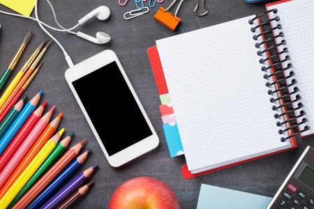 School and office supplies, smartphone and apple on blackboard background. Top view with copy space