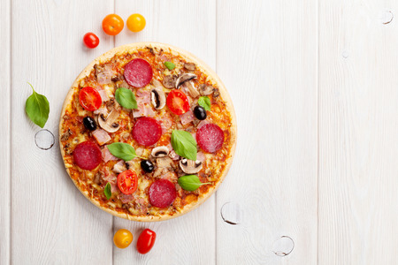 wooden board: Italian pizza with pepperoni, tomatoes, olives and basil on wooden table. Top view with copy space