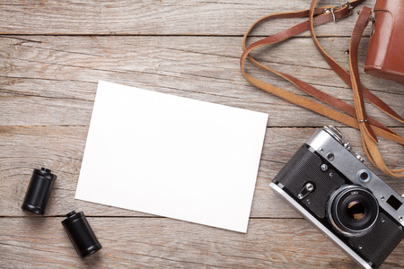 photo: Vintage film camera and blank photo frame on wooden table. Top view Stock Photo