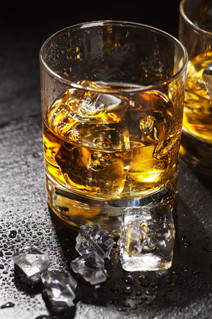 drinks on bar: Glasses of whiskey with ice on black stone table
