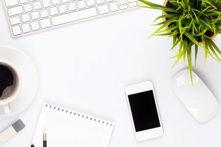 Tavolo Scrivania con computer, forniture, fiori e tazza di caffè. Vista dall'alto con spazio di copia Archivio Fotografico