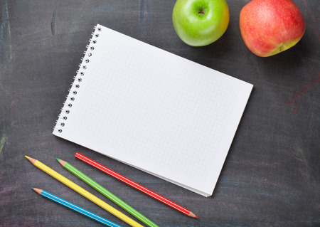Blank notepad, colorful pencils and apples on blackboard background. Top view with copy space Stock Photo