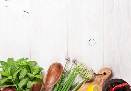 cooking utensil: Fresh herbs and spices on wooden table. Top view with copy space