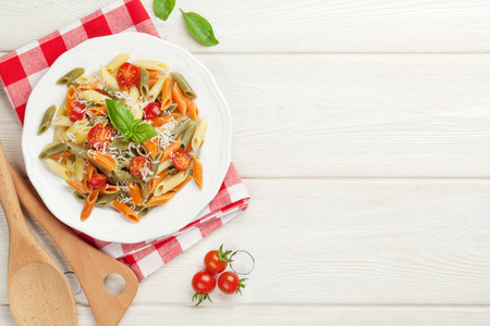 dish: Colorful penne pasta with tomatoes and basil on wooden table. Top view with copy space