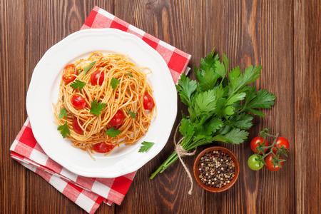 견해: 나무 테이블에 토마토, 파 슬 리와 스파게티 파스타. 평면도