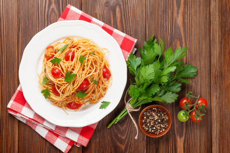 fresh pasta: Spaghetti pasta with tomatoes and parsley on wooden table. Top view Stock Photo
