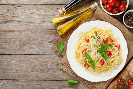 Spaghetti pasta with tomatoes and parsley on wooden table. Top view with copy space Standard-Bild