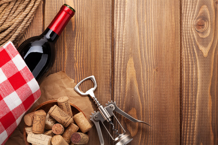 Red wine bottle, corks and corkscrew over wooden table background. Top view with copy space Stockfoto