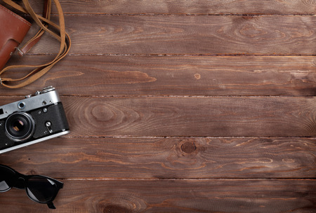 trompo de madera: Cámara y gafas de sol en la mesa escritorio de madera. Vista superior con espacio de copia