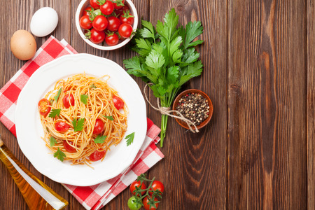 Spaghetti pasta with tomatoes and parsley on wooden table. Top view with copy space 写真素材