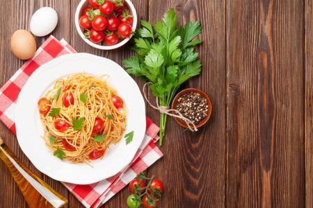 pasta: Pastas del espagueti con los tomates y el perejil en mesa de madera. Vista superior con espacio de copia Foto de archivo