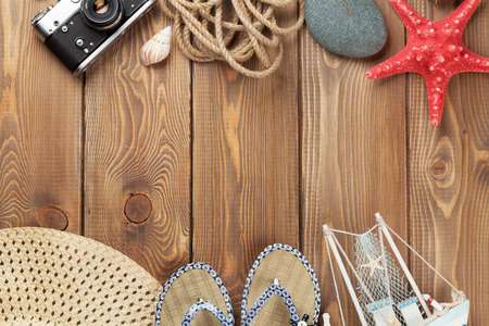 beach view: Travel and vacation items on wooden table. Top view with copy space