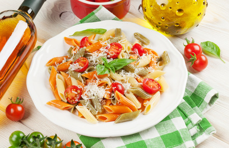 white towel: Colorful penne pasta and white wine on wooden table