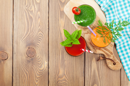 background wood: Fresh vegetable smoothie on wooden table. Tomato, cucumber, carrot. Top view with copy space