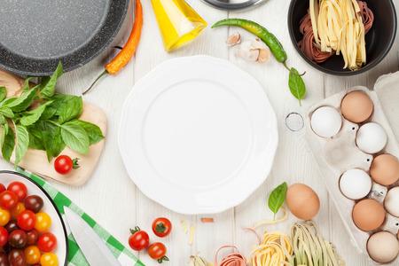 pasta: Ingredientes para cocinar Pasta y utensilios de mesa de madera.