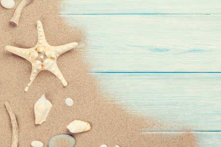 blue top: Sea sand with starfish and shells on wooden table.