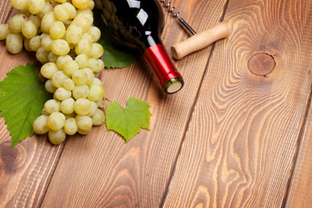 white wine: Red wine bottle and bunch of white grapes on wooden table background