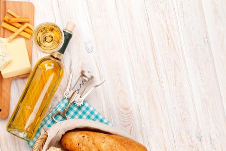 흰색 나무 테이블 배경에 화이트 와인, 치즈와 빵.