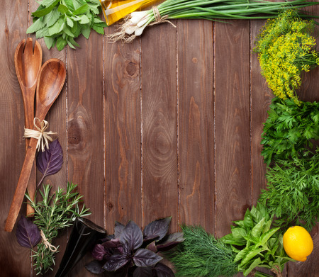 cutting boards: Fresh garden herbs frame on wooden table. Top view with copy space Stock Photo