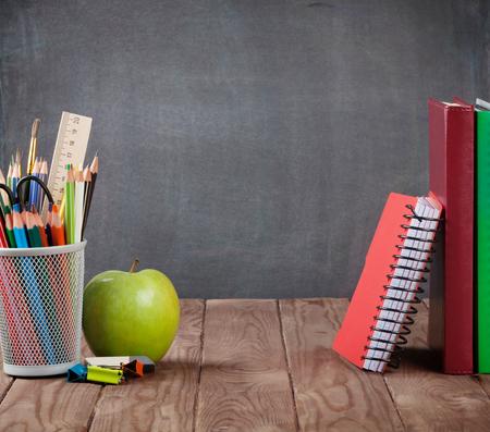 pizarron: Escuela y útiles de oficina en la mesa de clase delante de la pizarra. Ver con copia espacio
