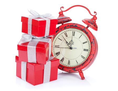 reloj: Reloj de la Navidad y tres cajas de regalo. Aislado en el fondo blanco