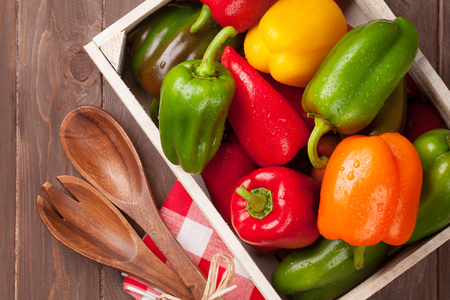 Fresh colorful bell pepper in box on wooden table. Top view Banco de Imagens