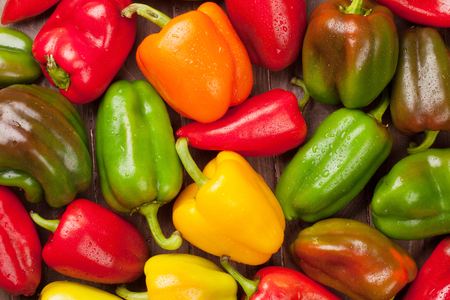 Fresh colorful bell peppers on wooden table. Top view Standard-Bild