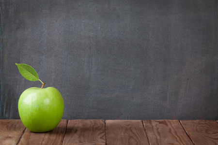 Apple fruit on classroom table in front of blackboard. View with copy space Archivio Fotografico
