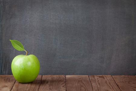 Pomme fruit sur la table en classe devant tableau noir. Voir avec copie espace