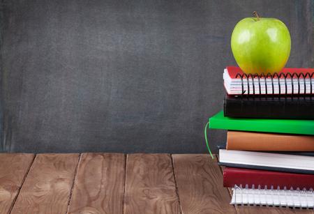 utiles escolares: Escuela y útiles de oficina en la mesa de clase delante de la pizarra. Ver con copia espacio