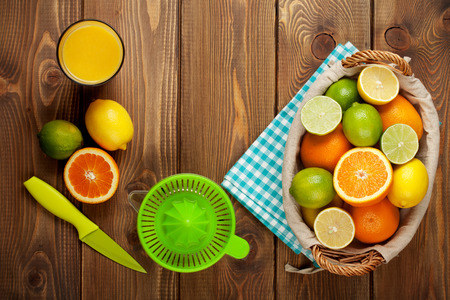 juice squeezer: Citrus fruits and glass of juice. Oranges, limes and lemons. Top view over wood table background Stock Photo