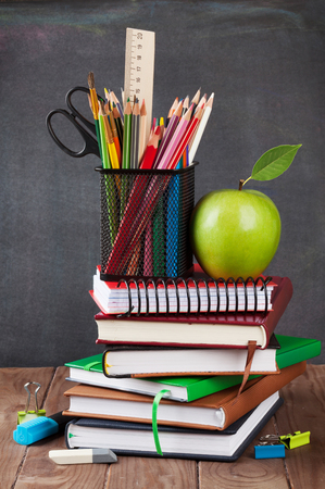 pizarron: School and office supplies on classroom table in front of blackboard