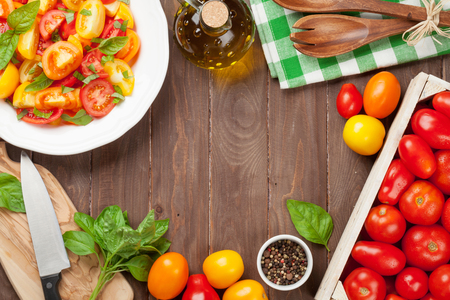 fresh vegetable: Fresh colorful tomatoes and basil salad on wooden table. Top view with copy space