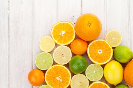 Zitrusfrüchte. Orangen, Limetten und Zitronen. Über Holztisch Hintergrund mit Kopie Raum