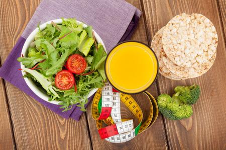 cinta metrica: Comida sana y cinta métrica sobre la mesa de madera. Condición física y salud Foto de archivo