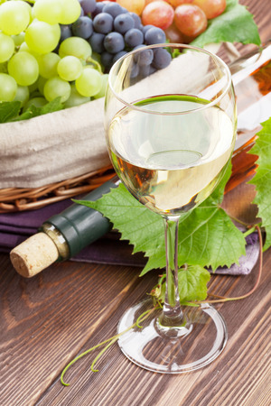 white wine glass: White wine glass, bottle and grapes on wooden table Stock Photo