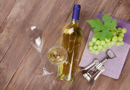 food and wine: Bunch of grapes, white wine and corkscrew on wooden table background