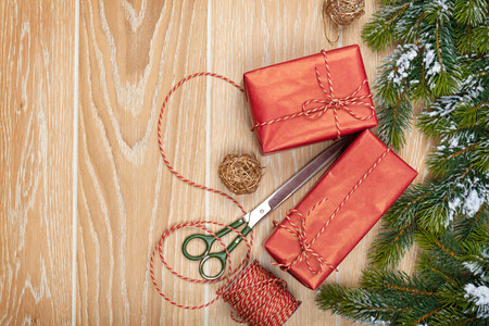 christmas tree presents: Christmas presents wrapping and snow fir tree over wooden table background with copy space