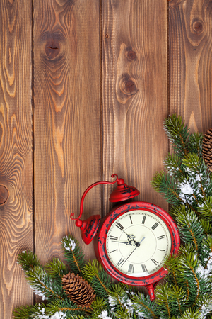 twelve month old: Christmas wooden background with clock, snow fir tree and copy space Stock Photo