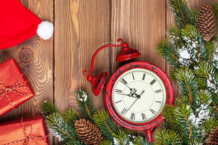 wood box: Christmas wooden background with clock, snow fir tree, gift boxes and santa hat