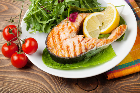Grilled salmon and salad on wooden table
