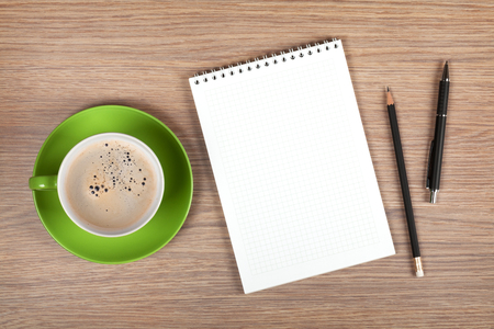 note pad and pen: Blank notepad and coffee cup on office wooden table Stock Photo