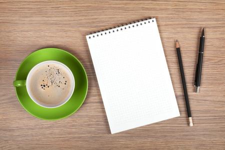 boligrafos: Libreta en blanco y una taza de café en la mesa de madera oficina